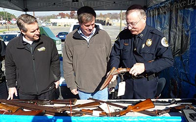Dollar General Vice President Steve Brophy (left) and Mayor Karl Dean (center) watch as Chief Steve Anderson examines a sawed-off shotgun turned in during a Gift Cards for Guns event Nov. 17, 2012. (Photo courtesy of Metro Nashville Police)