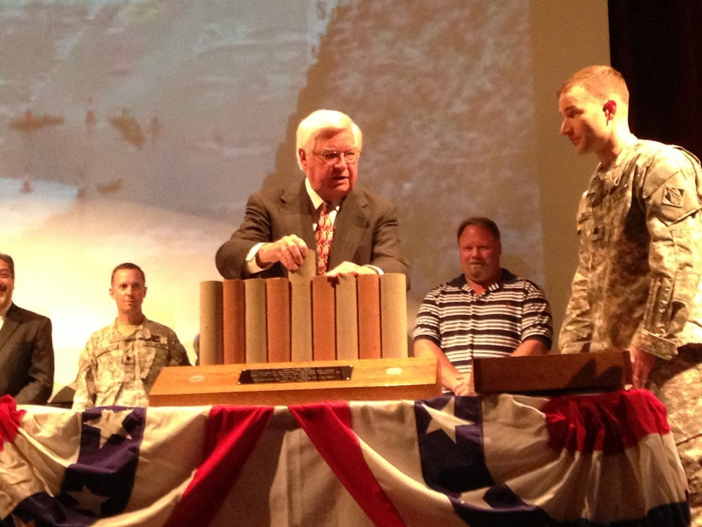 Congressman Hal Rogers of Kentucky's 5th District inserts the last pile in a model of the concrete barrier wall constructed in the embankment at Wolf Creek Dam. Rogers gave the keynote address at a completion ceremony April 19, 2013 at the Russell Springs Auditorium and Natatorium in Russell Springs, Ky. (Photo by Lee Roberts)