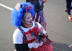 This clown hands out U.S. Flags out along the parade route in 2012. (Photo by Lee Roberts)