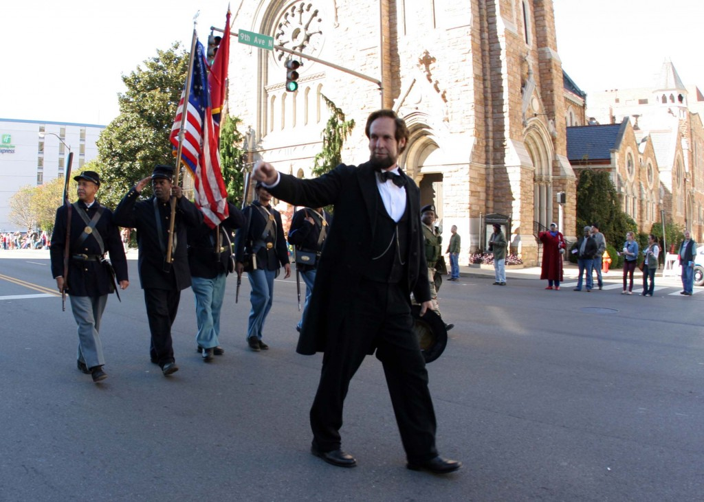 A President Abraham Lincoln reenactor walks down Broadway during the Nashville Veteran's Day Parade Nov. 11, 2013. (Photo by Lee Roberts)