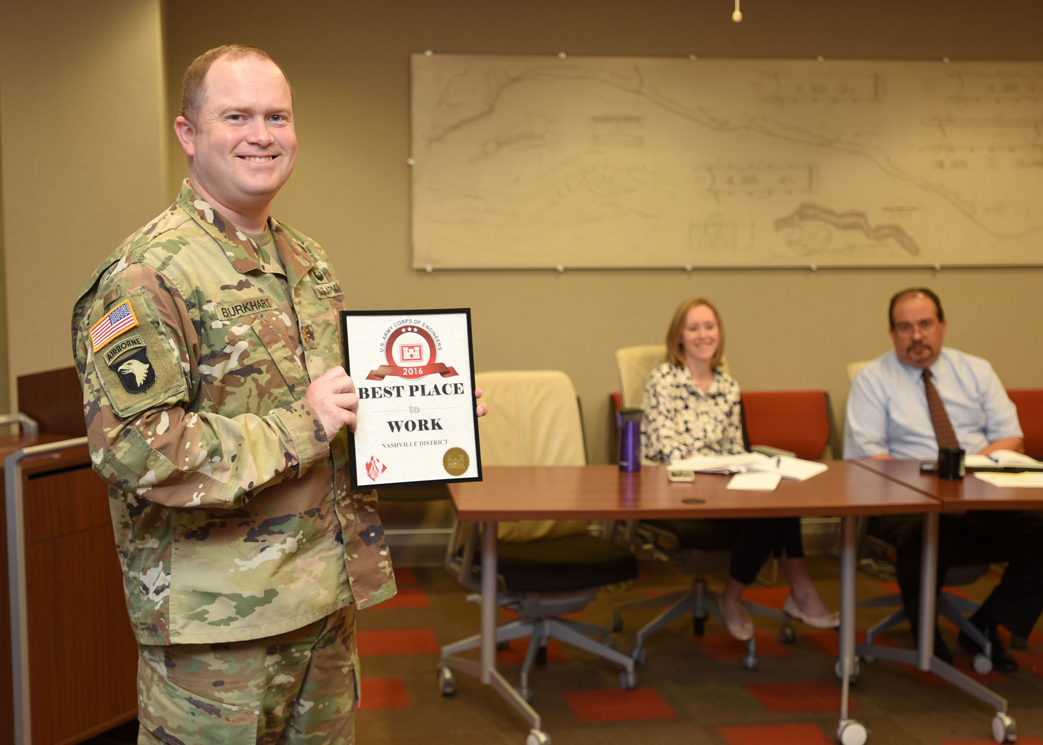 """Maj. Christopher Burkhart, U.S. Army Corps of Engineers Nashville District deputy commander, shows off the """"Best Place to Work in USACE"""" Award at the district's staff meeting Sept. 11, 2017 in Nashville, Tenn. The award was in the medium size agency category based on employee responses in the 2016 Federal Employee Viewpoint Survey. Nine awards were presented by the U.S. Army Corps of Engineers Headquarters to organizations in this category. (Photo by Lee Roberts)"""